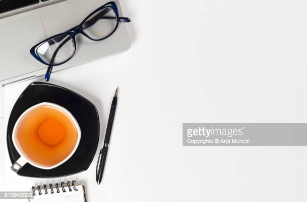 Directly above view of office desk table with computer, notebook, eyeglasses and green tea cup