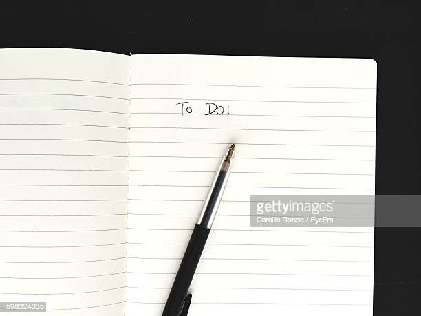 Directly Above View Of Open Book With Text And Pen On Table