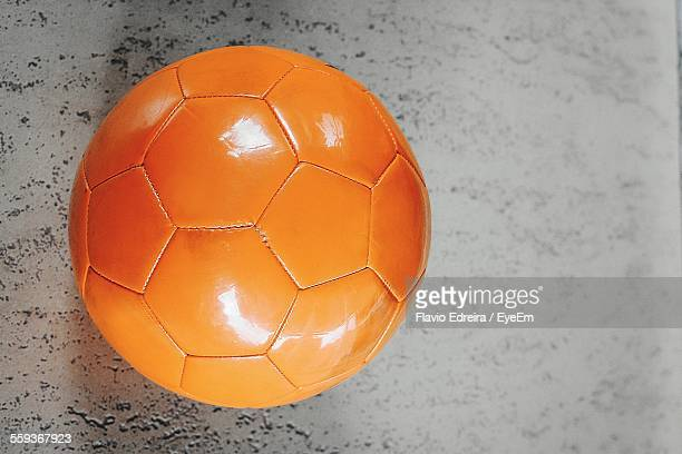 Directly Above View Of Orange Soccer Ball On Concrete Flooring