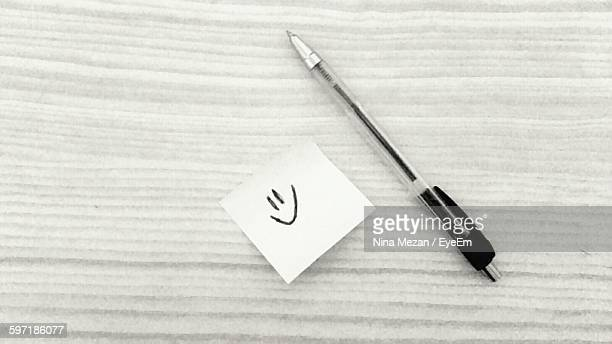 Directly Above View Of Pen And Smiley Face On Paper