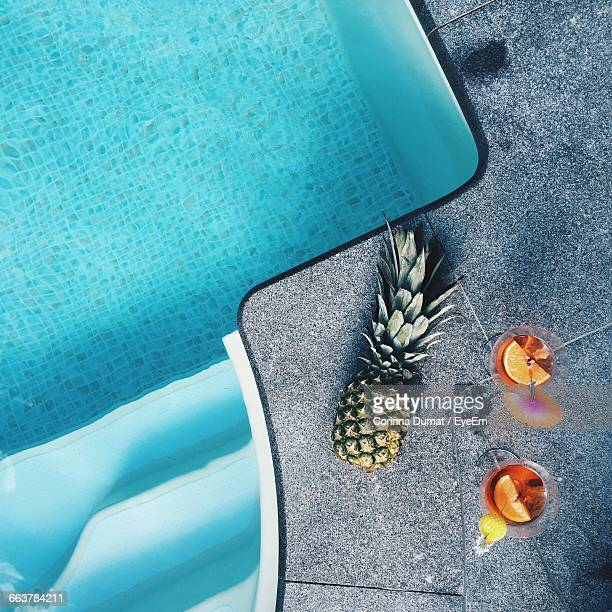 Directly Above View Of Pineapple And Drinks At Poolside