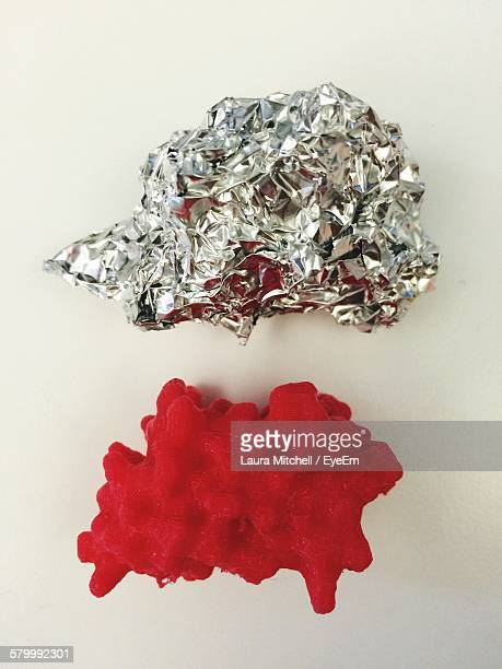 Directly Above View Of Red Protein With Crumpled Foil Against White Background