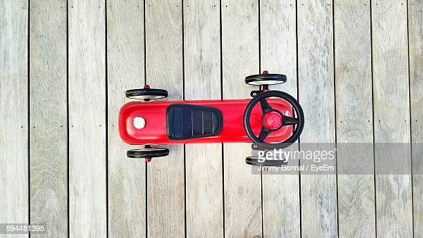 Directly Above View Of Red Toy Car On Boardwalk