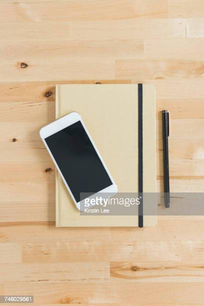 Directly above view of smart phone and personal organizer and pen on wooden desk