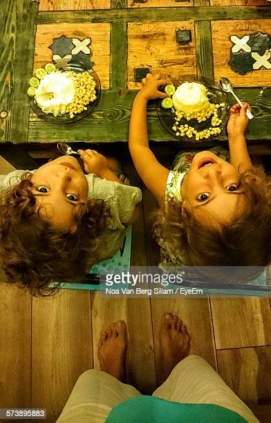 Directly Above View Of Twin Girls Eating Breakfast On Table