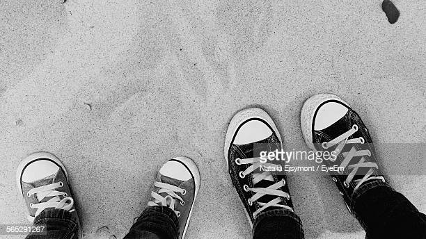 Directly Above View Of Woman And Girl With Canvas Shoes Standing On Beach Sand