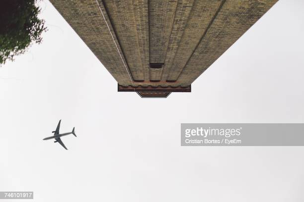 Directly Below Shot Of Airplane By Historic Building Against Clear Sky