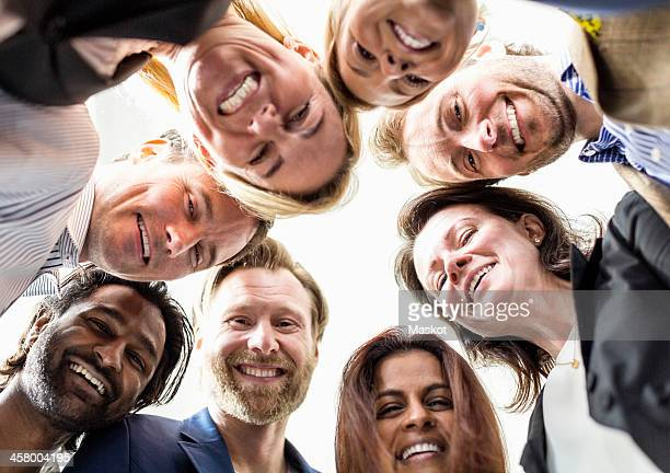 Directly below shot of business people forming huddle against clear sky