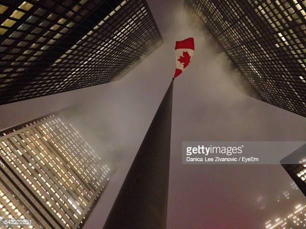 Directly Below Shot Of Canadian Flag Waving On Tower