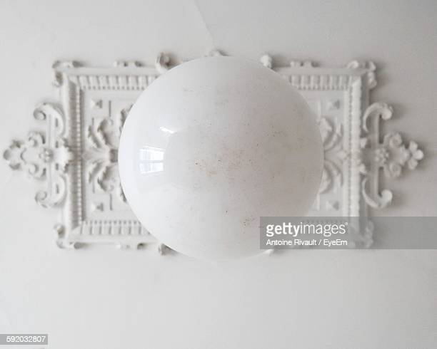 Directly Below Shot Of Electric Lamp Hanging On Ceiling