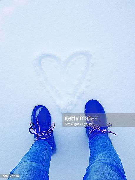 Directly Below Shot Of Man Standing By Heart Shape Drawn On Snow Covered Field