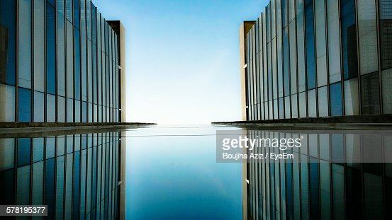 Directly Below Shot Of Modern Buildings Reflecting On Glass Wall
