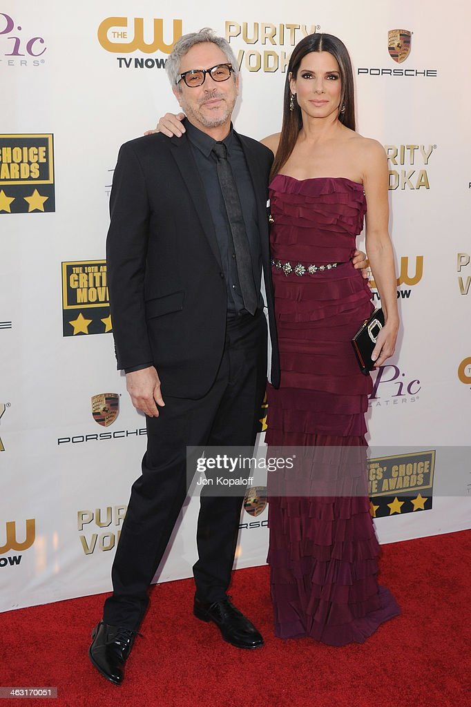 Director Alfonso Cuaron and actress Sandra Bullock arrive at the 19th Annual Critics' Choice Movie Awards at Barker Hangar on January 16, 2014 in Santa Monica, California.