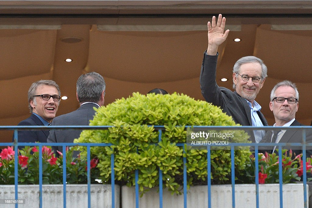 US director and President of the Feature Film Jury, Steven Spielberg, waves as he poses on May 14, 2013 with General Delegate of the Cannes Film Festival Thierry Fremaux (R) and Austrian actor and member of the Feature Film Jury Christoph Waltz (L) on the balcony of the Grand-Hyatt Martinez Hotel in Cannes on the eve of the 66th edition of the Cannes Film Festival. Cannes, one of the world's top film festivals, opens on May 15 and will climax on May 26 with awards selected by a jury headed this year by Hollywood legend Steven Spielberg. AFP PHOTO / ALBERTO PIZZOLI