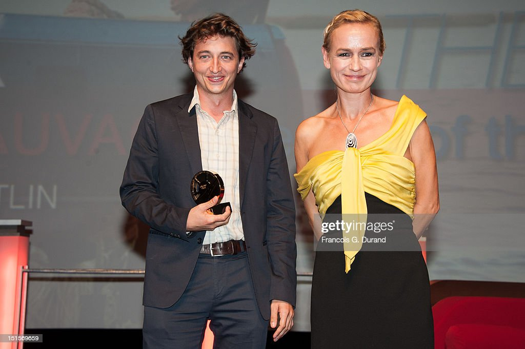 Director Benh Zeitlin poses with Sandrine Bonnaire during the closing ceremony of the 38th Deauville American Film Festival on September 8, 2012 in Deauville, France.
