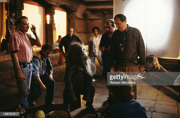 Director Bernardo Bertolucci with an actor in a baby elephant costume on the set of the film 'Little Buddha' circa 1992