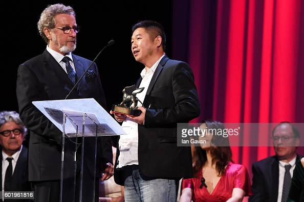 Director Bing Wang holds a speech as he receives the Orizzonti Award for Best Screenplay for 'Ku Qian' with jury member Robert Guediguian during the...