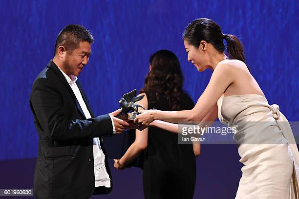 Director Bing Wang receives the Orizzonti Award for Best Screenplay for 'Ku Qian' from jury member Moon Sori during the closing ceremony of the 73rd...