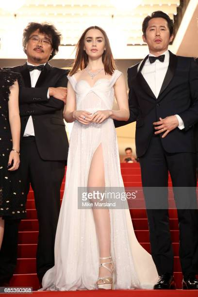 Director Bong Joonho Lily Collins and Steven Yeun departs the 'Okja' premiere during the 70th annual Cannes Film Festival at Palais des Festivals on...