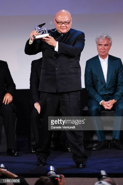 Director Cai Shangjun of 'Ren Shan Ren Hai' accepts the Silver Lion for Best Director as musician David Byrne looks on during the Closing Ceremony...