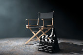 Director Chair, Movie Clapper and Megaphone in the volumetric light on a black background. 3d Rendering