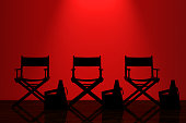 Director Chairs, Movie Clappers and Megaphones with Red Backlight in front of Wall in dark room. 3d Rendering