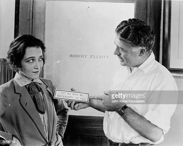 Director Clarence Brown presents a plaque to actress Pauline Frederick on the set of 'Smouldering Fires' in front of Robert Elliott's office door The...