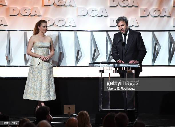 "Director Denis Villeneuve accepts the Feature Film Nomination Plaque for ""Arrival"" from actress Amy Adams onstage during the 69th Annual Directors..."