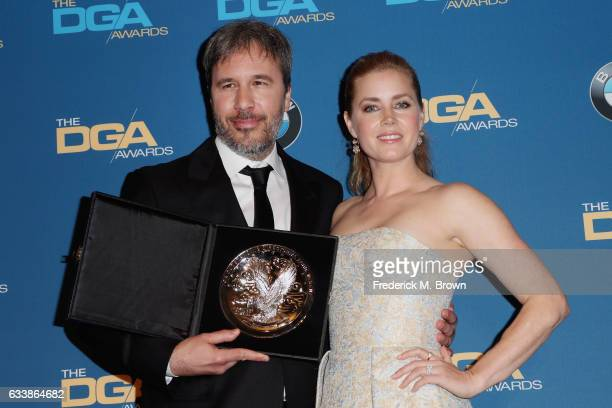 "Director Denis Villeneuve recipient of the Feature Film Nomination Plaque for ""Arrival"" poses with actress Amy Adams in the press room during the..."