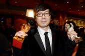Director Diao Yinan poses with his Golden Bear for Best Film and a Silver Bear after the closing ceremony during 64th Berlinale International Film...