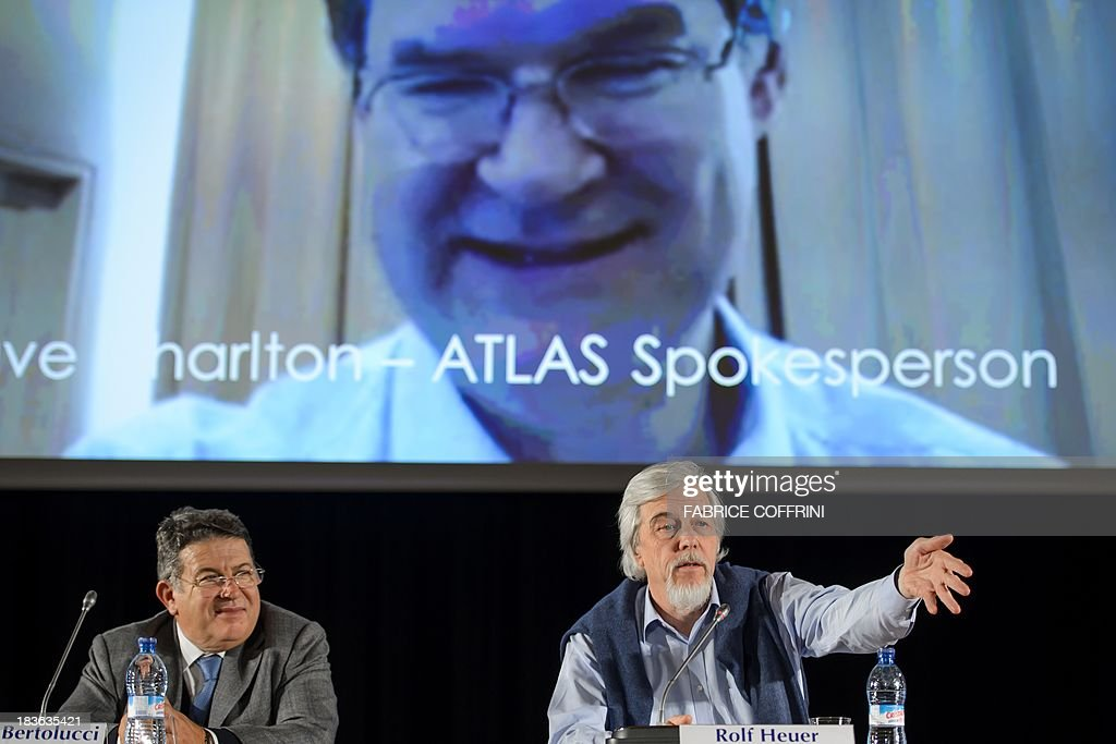 Director for Research and Scientific Computing Sergio Bertolucci (L) and CERN Director General Rolf Heuer (R) gesture beneath a TV screen broadcasting live ATLAS's CERN experiment spokesperson Dave Charlton during a press conference after the annoucement of the winners of the Nobel Prize for Physics on October 8, 2013 in Meyrin near Geneva. Peter Higgs of Britain and Francois Englert of Belgium won the Nobel Prize for Physics for conceiving of the so-called 'God particle' which confers mass. The presumed particle was discovered last year by Europe's mega-scale physics lab at CERN, near Geneva, after a decades-long search.