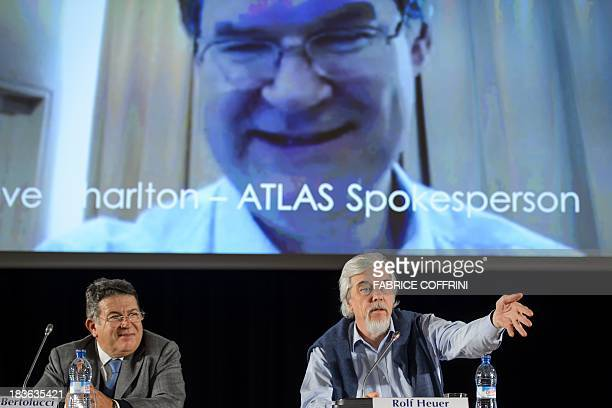 Director for Research and Scientific Computing Sergio Bertolucci and CERN Director General Rolf Heuer gesture beneath a TV screen broadcasting live...