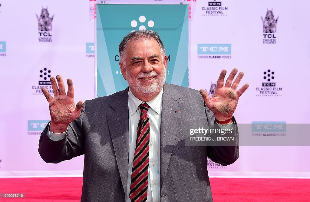 Director Francis Ford Coppola displays his hands after imprinting them into the cement at his Hand and Footprint Ceremony in front of the TCL theater in Hollywood, California on April 29, 2016. The US film director was honored as part of the 2016 TCM Classic Film Festival. / AFP / FREDERIC