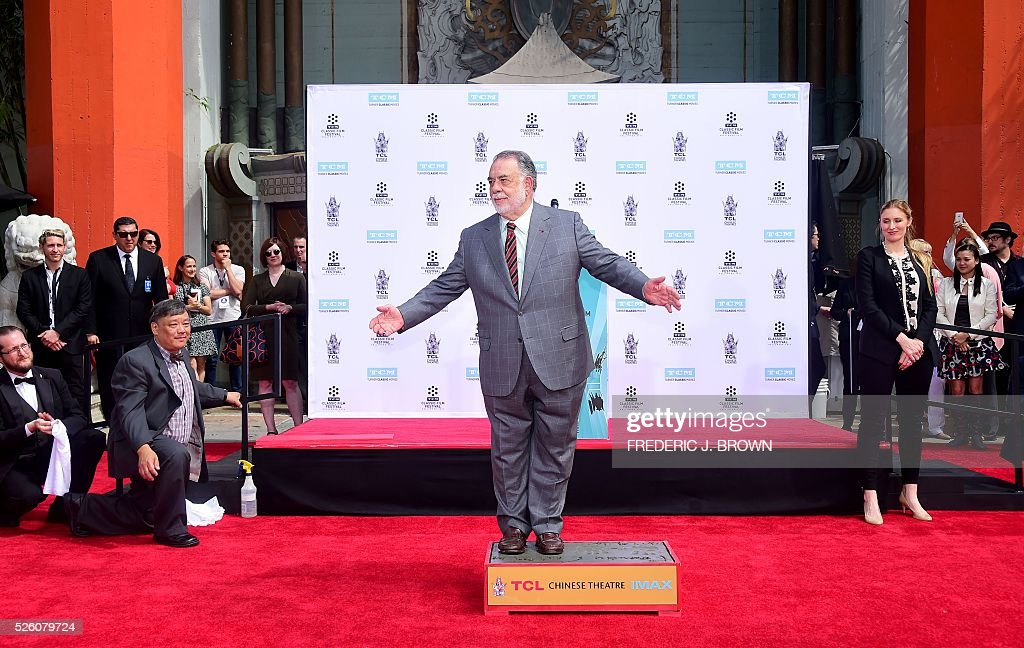 Director Francis Ford Coppola gestures while standing on the cement at his Hand and Footprint Ceremony in front of the TCL theater in Hollywood, California on April 29, 2016. The US film director was honored as part of the 2016 TCM Classic Film Festival. / AFP / FREDERIC
