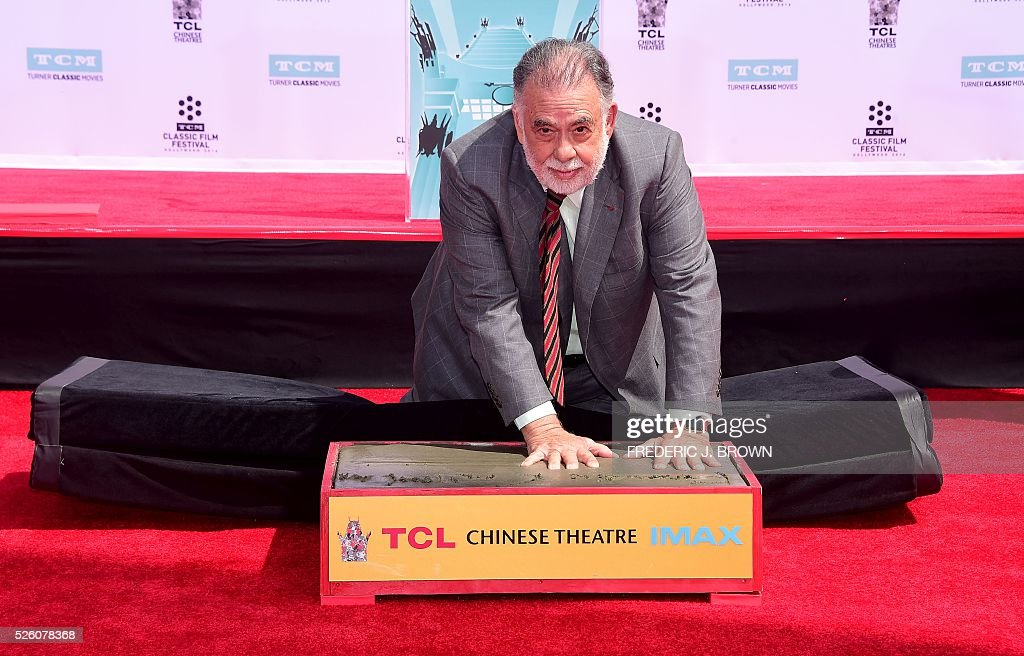Director Francis Ford Coppola imprints his hands into the cement at his Hand and Footprint Ceremony in front of the TCL theater in Hollywood, California on April 29, 2016. The US film director was honored as part of the 2016 TCM Classic Film Festival. / AFP / FREDERIC