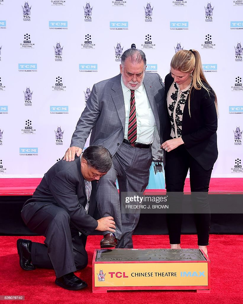 Director Francis Ford Coppola is assisted as he steps onto the cement at his Hand and Footprint Ceremony in front of the TCL theater in Hollywood, California on April 29, 2016. The US film director was honored as part of the 2016 TCM Classic Film Festival. / AFP / FREDERIC