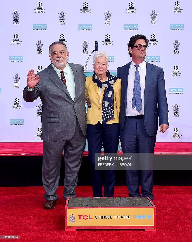 Director Francis Ford Coppola poses with his wife Eleanor and son Roman at his Hand and Footprint Ceremony in front of the TCL theater in Hollywood, California on April 29, 2016. The US film director was honored as part of the 2016 TCM Classic Film Festival. / AFP / FREDERIC