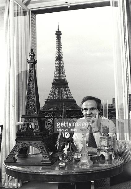 Director Francois Truffaut in his Paris apartment posing in front of his collection of miniature Eiffel Tower the true appearing behind him by the...
