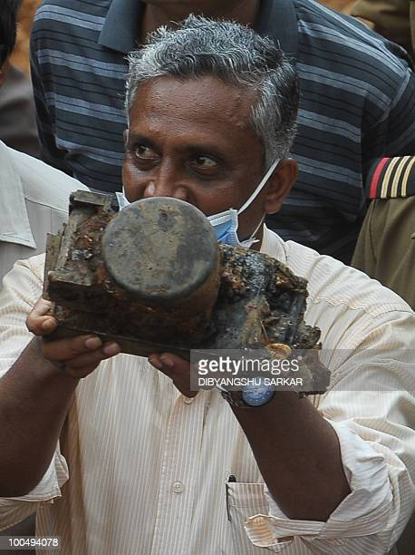 A Director General of Civil Aviation official holds an aircraft part which officials claim is the 'black box' of the doomed Air India Express flight...