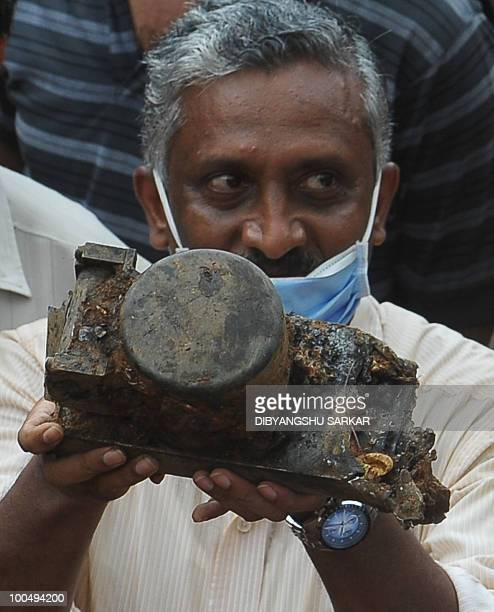 A Director General of Civil Aviation official holds up an aircraft part which officials claim is the 'black box' of the doomed Air India Express...