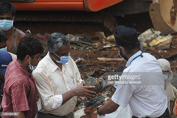 A Director General of Civil Aviation official inspects an aircraft part which officials claim is the 'black box' of the doomed Air India Express...