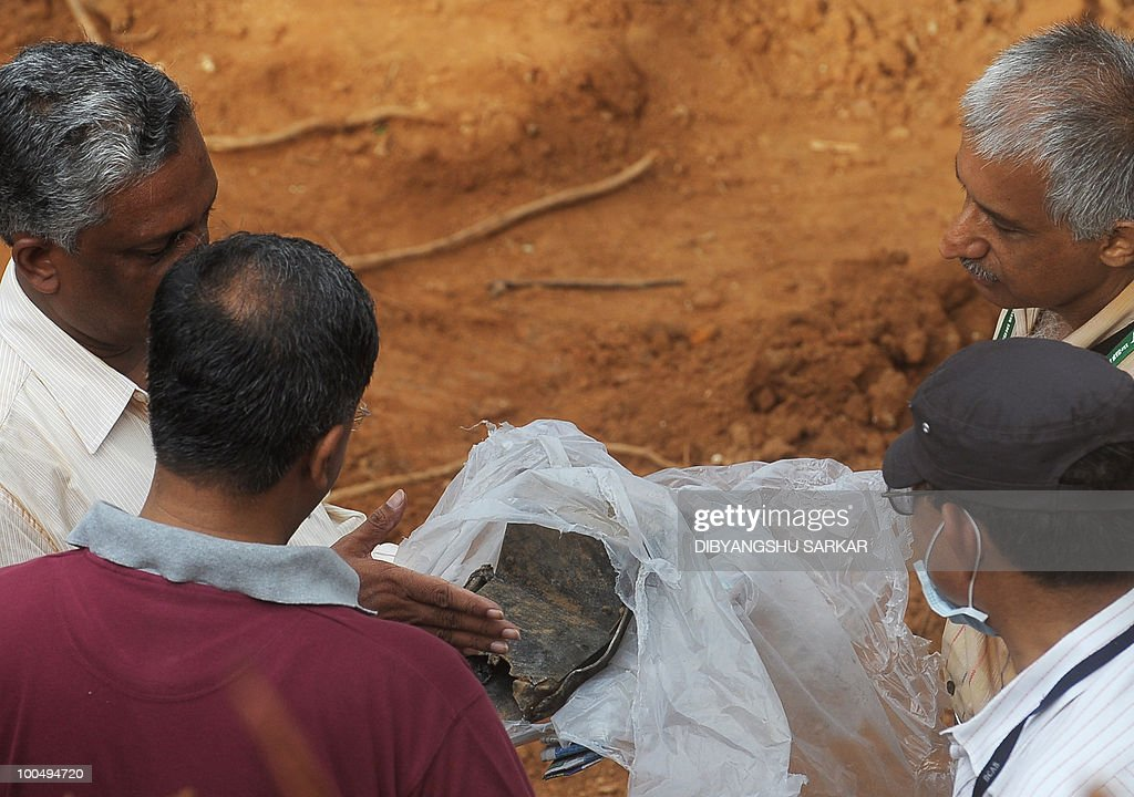 Director General of Civil Aviation (DGCA) officials inspect an aircraft part which officials claim is a 'black box' component of the doomed Air India Express flight 812, discovered at the crash site in Mangalore on May 25, 2010. Investigators recovered May 25 the 'black box' digital flight recorder that holds crucial clues to the crash of an Air India Express plane in southern India that killed 158 people. The discovery followed an intense three-day search that began hours after the Boeing 737-800, flying from Dubai to the city of Mangalore, overshot the runway May 22, plunged into a gorge and burst into flames. AFP PHOTO/Dibyangshu Sarkar