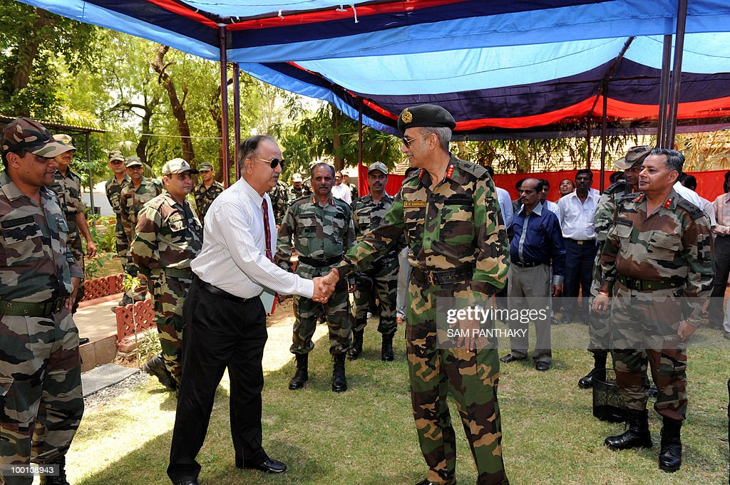 Director General of India's National Cadet Corps (NCC) Lieutenant General R.K. Karwal (C) shakes hands with Group Captain MG Mehta, Public Relations Officer, Ministry of Defence before addressing media representatives at NCC Directorate (Gujarat), Cantonment in Ahmedabad on May 21, 2010. Karwal was in the western Indian city to oversee NCC activities being conducted in Gujarat. AFP PHOTO/Sam PANTHAKY