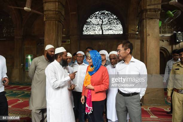 Director General of UNESCO Irina Bokova interacts with a volunteer as UNESCO's New Delhi Director Shigeru Aoyagi looks on during their visit to the...