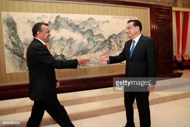 Director general of World Health Organisation Tedros Adhanom Ghebreyesus and Chinese Premier Li Keqiang walks towards each other to shake hands...