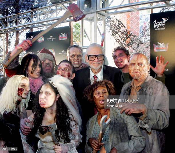 Director George A Romero is surrounded by actors portraying zombies as he arrives for the world premiere of his movie 'Land of the Dead' during the...