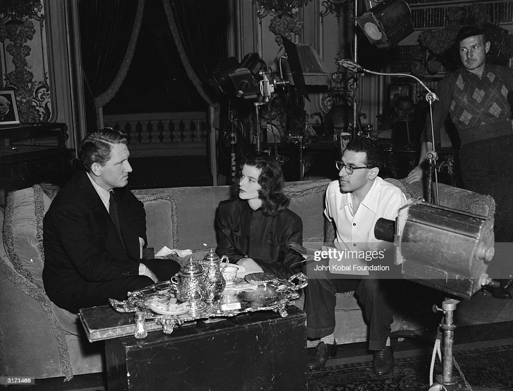 Director George Cukor discusses the film script with stars Katharine Hepburn (1907 - 2003) and Spencer Tracy (1900 - 1967) on the set of the MGM film 'Keeper of the Flame'. Silverware is laid out on the coffee table in front of them.