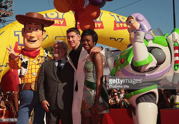Director George Lucas his son Jet and Mellody Hobson pose with Toy Story characters Woody and Buzz Lightyear as they attend the Golden Lion Lifetime...