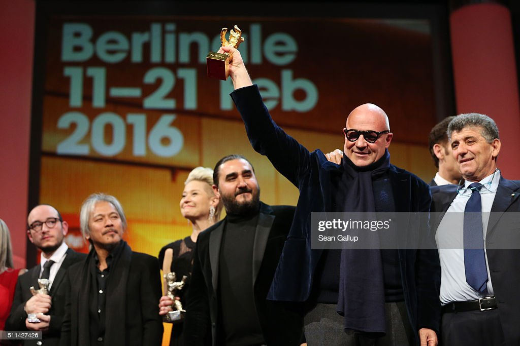 Director Gianfranco Rosi poses with protagonist Pietro Bartolo after receiving the Golden Bear for Best Film for the film 'Fuocoammare ' on stage...