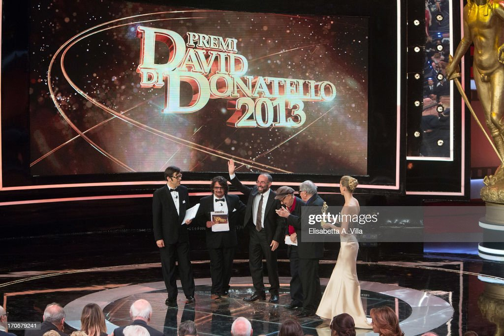 Director <a gi-track='captionPersonalityLinkClicked' href=/galleries/search?phrase=Giuseppe+Tornatore&family=editorial&specificpeople=2761023 ng-click='$event.stopPropagation()'>Giuseppe Tornatore</a> (C) receives the award for the best movie 'La Migliore Offerta' during 2013 Premi David di Donatello Ceremony Awards at Dear RAI Studios on June 14, 2013 in Rome, Italy.